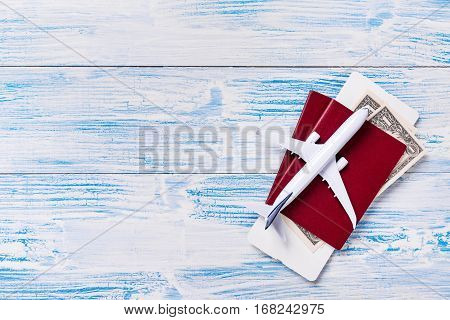 White Blank Model Of Passenger Plane, Passports With Boarding Pass And Dollars On Blue Wooden Backgr
