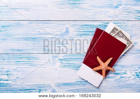 Passports With Boarding Pass And Dollar Banknotes On Blue Wooden Background
