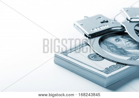 Pair Of Handcuffs Closeup On Dollar And Euro Banknotes Stacks.  Blue Tone