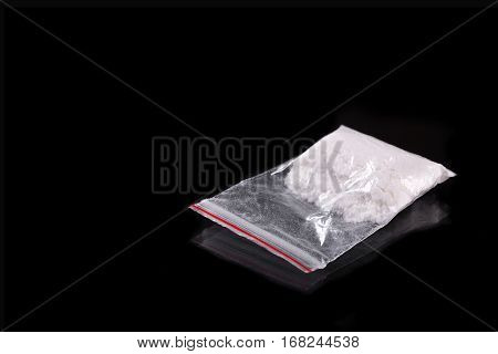 Cocaine In Plastic Packet On Black Background