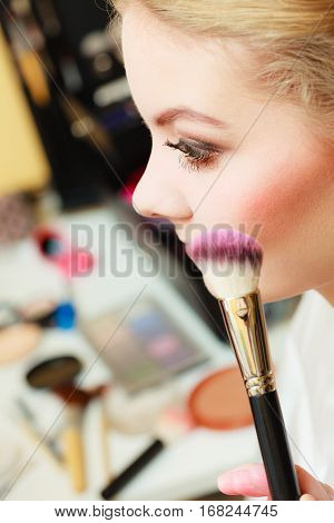 Visage concept. Close up woman getting make up on cheeks. Applying blush with brush.
