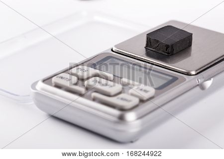 Block Of Hashish On Digital Scales Over White Background