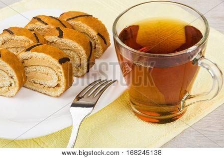 Swiss Roll Cake In Dish On Yellow Towel, Tea