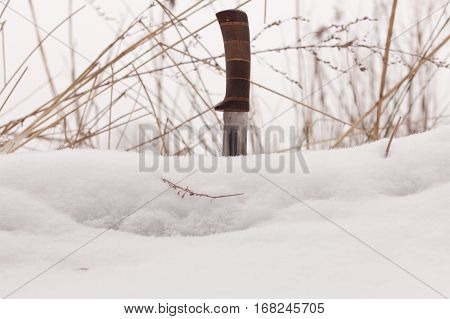 sharp hunting knife, stuck in the snow