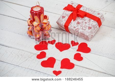 St. Valentine's Day: one carved candle, hearts from felt and a gift with a red tape. It is made with own hands