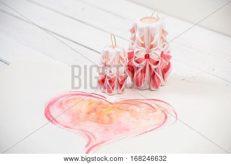 St. Valentine's Day: two pink carved candles, one big pink heart. One love for two.