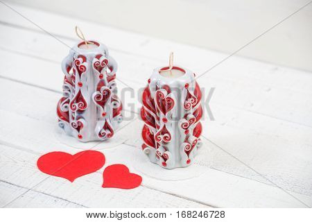 St. Valentine's Day: two carved candles and two felt hearts as love symbol. Two hearts fight as one