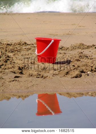 A Red Plastic Bucket On A Sandbank With A Wave At The Background