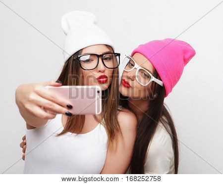 Two teenage girls friends in hipster outfit make selfie on a phone.