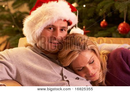 Tired Couple Relaxing In Front Of Christmas Tree