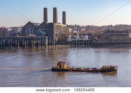 Cargo ship travelling up the Thames with a load of aggregates. Landscape shot taken on a bright sunny January afternoon.