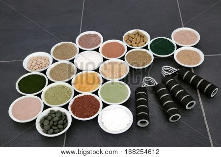 Body building powders and supplements in porcelain bowls with hand grippers over slate background.