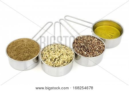 Hemp health food ingredients with powder, hulled seed, dried seeds and oil in metal measuring scoops on white  background.
