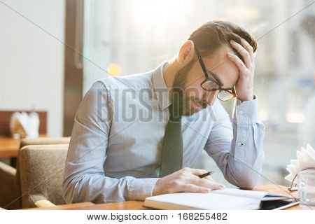 Bearded pensive businessman in shirt and tie sitting in cafe bent over notepad, holding head with his hand and thinking hard over solving company problems.