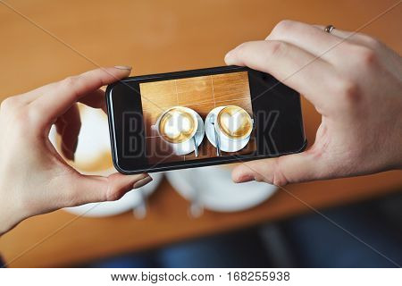Human hands holding smartphone and capturing two cups with cappuccino