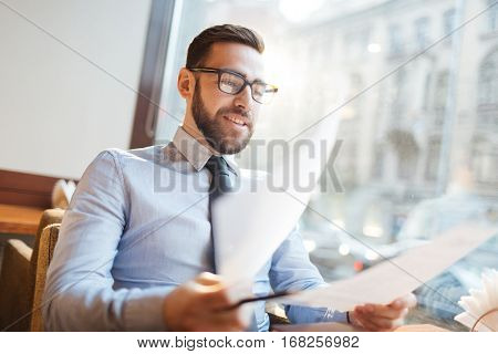 Low angle portrait of confident bearded businessman in shirt and tie sitting at cafe table, holding agreement papers and smiling, fully satisfied with new terms.