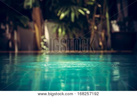 Swimming pool background in vintage style with ripples on turquoise water and tropical plants on blurred background