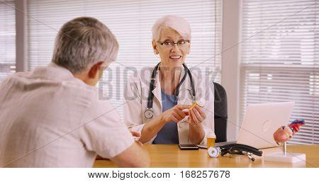 Senior Doctor Prescribing Medication To Elderly Patient