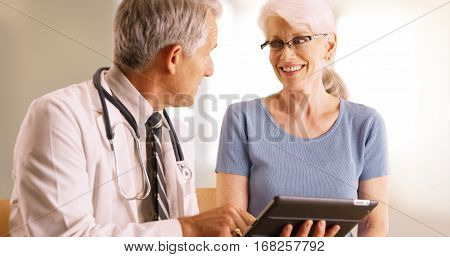 Doctor Going Over Elderly Woman's Health File In The Office With Tablet