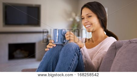 Millennial White Woman Happily Sits On Her Couch Drinking Coffee