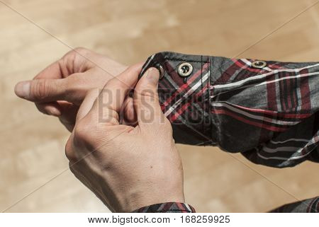 Buttoning the sleeve of a plaid shirt
