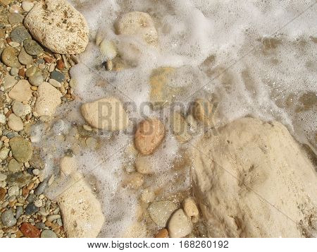 Pebble beach and foam of water on the coastline