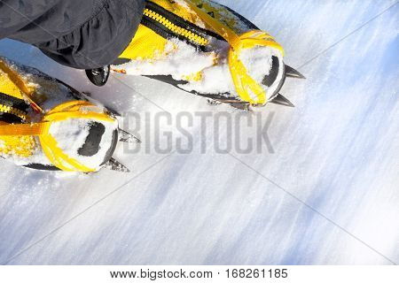 Pair of yellow high mountain boots with crampons in the snow.