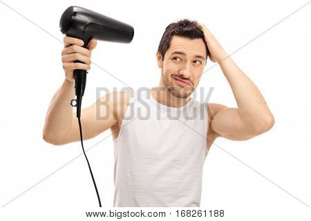 Handsome guy blow drying his hair isolated on white background