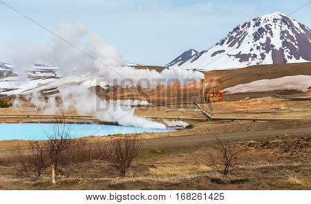 The geothermal power station Bjarnarflag in the Myvatn region in Iceland. Steam flows over the blue lake. In the background a snow-covered summit in the volcanic Krafla region.