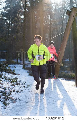 OLDENZAAL NETHERLANDS - JANUARY 22 2017: Unknown female athlete runs up a hill during a cross run in a forest