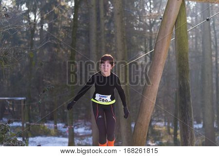 OLDENZAAL NETHERLANDS - JANUARY 22 2017: Unknown female athlete doing a cross run in a snowy forest