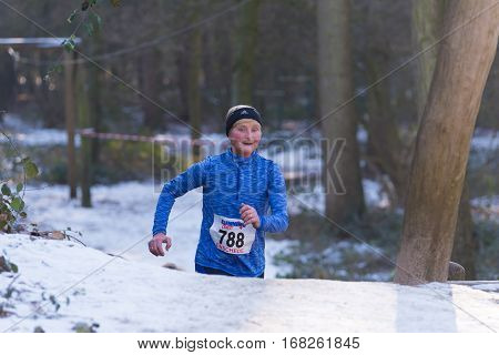 OLDENZAAL NETHERLANDS - JANUARY 22 2017: Unknown senior female athlete doing a cross run in a snowy forest