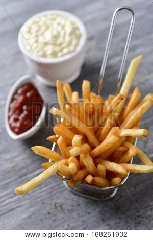some appetizing french fries served in a metallic basket and some bowls with mayonnaise and ketchup on a gray rustic wooden table