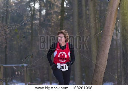 OLDENZAAL NETHERLANDS - JANUARY 22 2017: Unknown female athlete doing a cross run in a forest