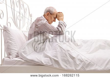 Depressed senior lying in bed with his head down isolated on white background