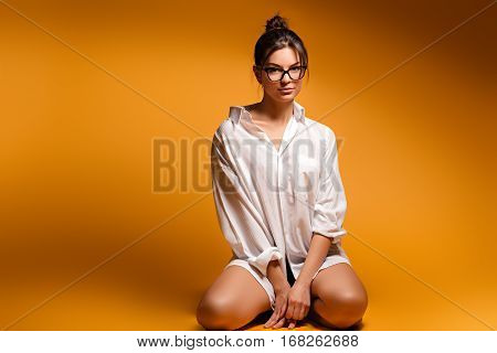 A young woman stand on a knees. Young pretty beautiful emotional girl in glasses posing on a yellow background. A young girl kneeling. Young girl sitting on a knees. woman sitting on a knees.