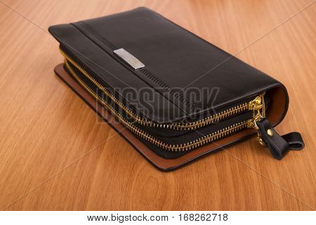 Men's black leather purse on two zippers on the wooden background
