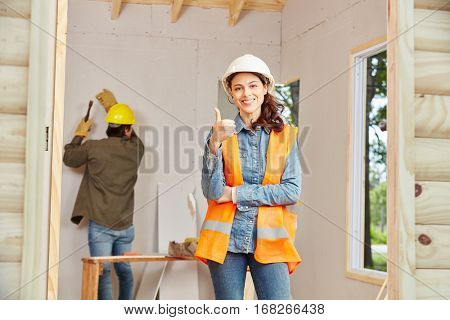 Young woman as apprentice of artisan holding thumbs up