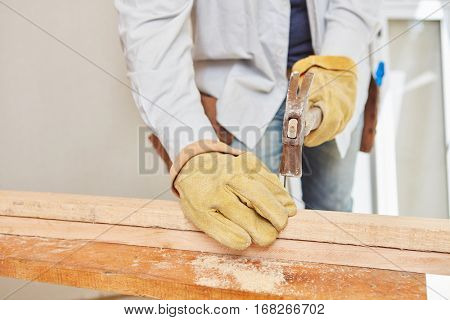 Carpenter hammering on wood during construction