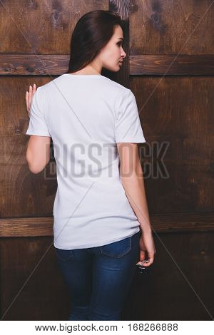 Young woman wearing blank white t-shirt with area for your logo or design, mock-up of template white t-shirt, back view