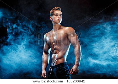 Strong bodybuilder with six pack, perfect abs, shoulders, biceps, triceps and chest, personal fitness trainer flexing his muscles in smoke