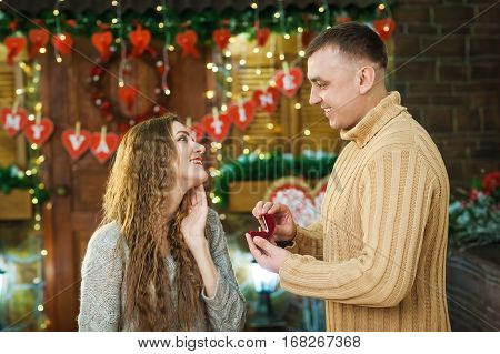 teenagers celebrate valentine's day. wife with tenderness looks at her husband, smiling and enjoy present