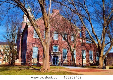 Historic brick building with a clock tower surrounded by large deciduous trees taken at the Wichita State University in Wichita, KS