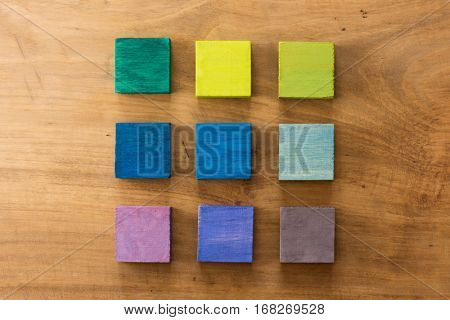 Index, menu or cover abstract back ground, consisting of nine hand painted colored wooden cubes on grungy wooden background with vintage taste.  blue, purple, green, yellow.