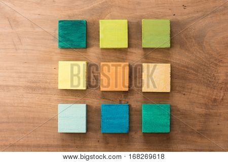 Index, menu or cover abstract back ground, consisting of nine hand painted colored wooden cubes on grungy wooden background with vintage taste. warm neutral colors. orange, gray, green, blue.