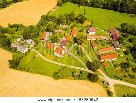Aerial view of small village in central Bohemia. Farms with beautiful gardens and fields in agricultural landscape. Living on Countryside, Czech Republic, Europe.