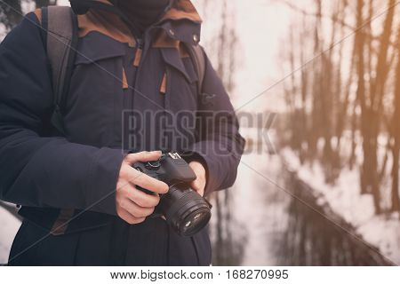 Man with camera close uo. Closeup of hand with camera. Photographer on sunny winter background. Lifestyle travel concept in vintage colors.