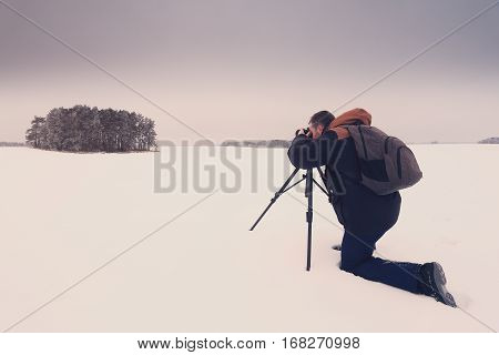 Photographer taking a picture. Man with camera on snow make landscape photo. Photographer on snowy background.