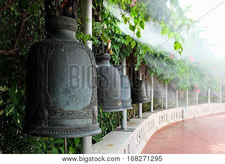 A curved row of traditional ornate iron or bronze bells at a buddhist monastery or temple, white smoke in the background.
