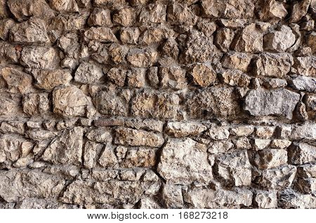 Stone wall texture / pattern for backgrounds. It looks antique and ancient, resembling being part of an old fortress or castle. The surface of each of the stacked blocks, which strongly vary in size and shape, is rough and natural.